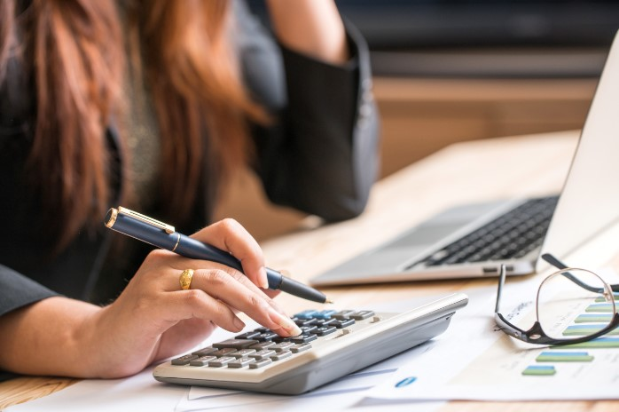 Business woman typing of calculator