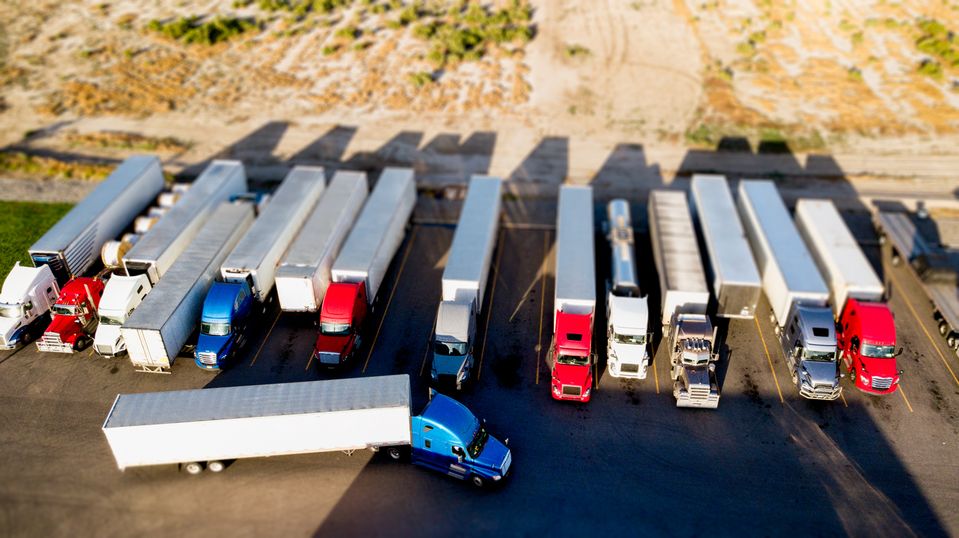 Drone View Using Tilt-Shift With Blurred Motion Of Semis Parked Side By Side In A Parking Lot